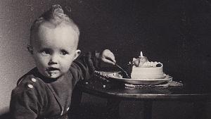 Säveltäjä Kaija Saariaho 1-vuotiaana kurkottaa vasemmalla kädellä, jossa lusikka syntymäpäiväkakkua