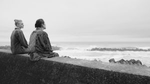Kaksi naista istuu kivimuurilla selin kameraan meren rannassa. Kuva elokuvasta Terveisiä Fukushimasta.