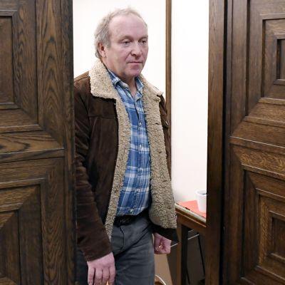 Teuvo Hakkarainen går genom en dörr.