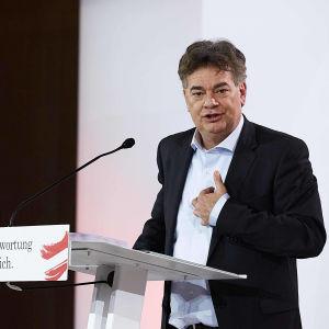 De Grönas ledare Werner Kogler står på scen och pratar med handen på bröstet, ÖVP:s Sebastian Kurtz tittar på från sidan.