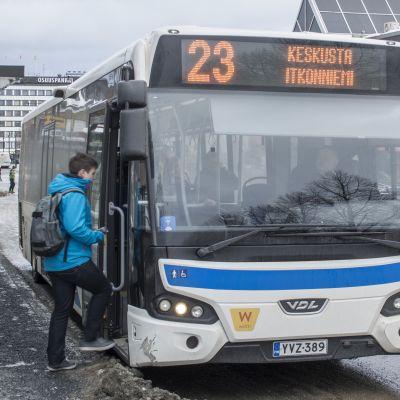 Poika nousee linja-autoon Kuopiossa