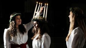 Tärna tänder ljusen i lucias krona, en annan tärna tittar på