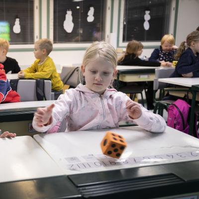 Lapsia istumassa pulpeteissaan koululuokassa. Oikealla lapsi heittää oranssia noppaa. Vasemmalla oleva lapsi tarkkailee vierestä.