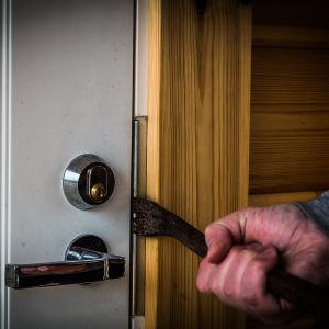 Någon bryter upp dörr med kofot