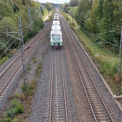 Bild tagen från bro över tågbana. Ett tåg kommer susande mot åskådaren.