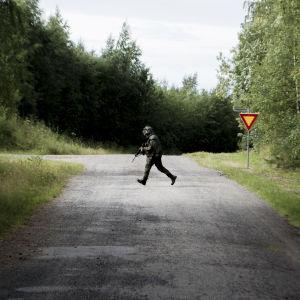 Varusmies juoksee tien poikki.