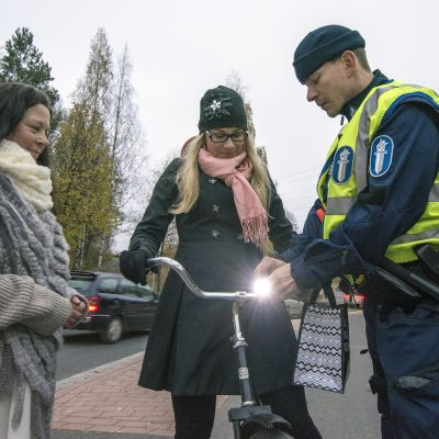 Liikenne-enkeli Mirja Vihuri ja vanhempi konstaapeli Petteri Serguskin antavat ilman valoja pyöräilleelle Iina Korhoselle pyörävalon.