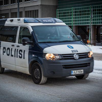 Poliisiauto kulkee lumisella kadulla.
