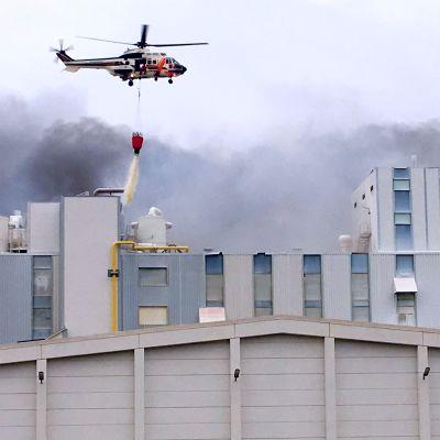 Rajavartiolaitoksen helikopteri tiputtaa vettä tehtaaseen.