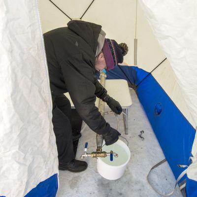 Mies ottaa vettä vesipisteestä Kuopion torilla.