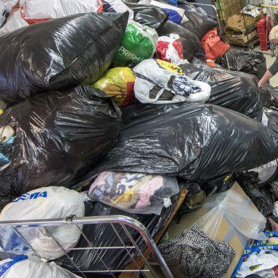 Lukuisia muovipusseja täynnä lahjoitusvaatteita.