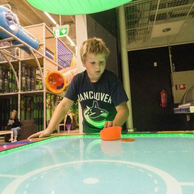 Poika pelaa ilmakiekkoa.