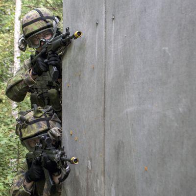 Varusmiehet tähtäävät nurkan takaa sotaharjoituksessa.