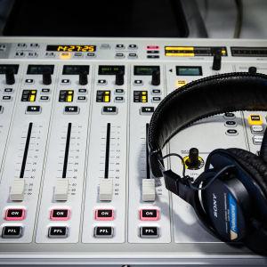 miksauspöytä, jonka päällä kuulokkeet