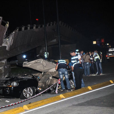 Räddningspersonal inspekterar en bil i staden  Guayaquil i Ecuador efter skalvet.