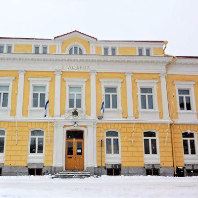 Ett gult gammalt stenhus, vinter, snö. Det står stadshus på byggnaden som har två våningar plus en mindre del högst upp i tredje våningen.