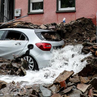 Bil som är täckt av byggmassor efter en storm. Vatten strömmar ut vid bilen