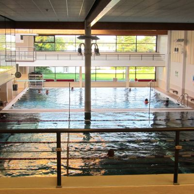 Människor simmar i simhall.