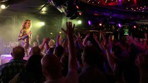 Lavalla euroviisurifaniristeilyn esiintyjä, lavan edessä innokasta juhlakansaa.