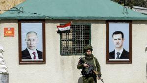 En rysk militärpolis, står mellan porträtt av Rysslands president och Syriens president, vid en vägspärr i Wafidiin. Vägspärren finns i utkanterna av Damaskus på vägen mot östra Ghouta.