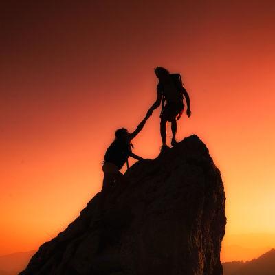 Två personer bestiger ett berg, den ena håller i den andra.