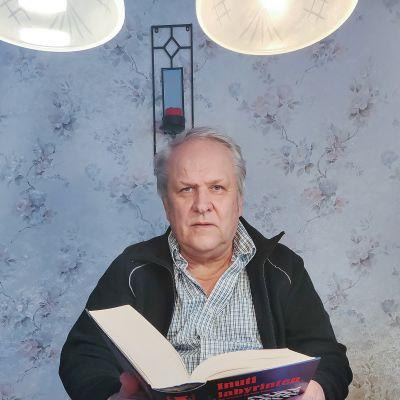 Kuvassa on Kari Poutiainen pöydän ääressä.
