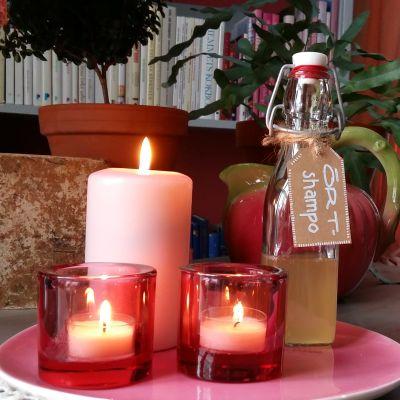 En flaska hemgjord örtshampo på ett bord med tända ljus.