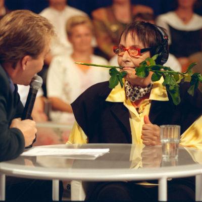 Marja Korhonen ruusu suussaan Tuttu Juttu -ohjelmassa Timo Koivusalon haastattelussa.