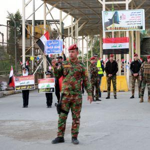 Irakiska militärer granskar bilar på väg in i den gröna zonen.