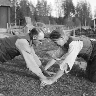 """Två män leker leken """"dra pissmyra"""". Bilden är tagen 1929 i Strömfors, Kejtala."""