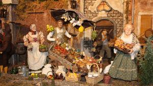 Yksityiskohta roomalaisesta jouluseimestä l'Arco di Dolabella (Dolabellan kaari): hedelmäkauppias.