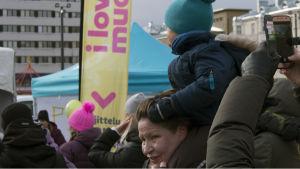 Lapsi istuu aikuisen harteilla I love muovi -tapahtumassa Lahden torilla.