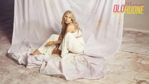 Evelina poseeraa studiossa valkeassa asussa valkeiden kankaiden ympäröimänä.