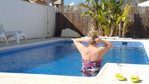 Nainen selin kameraan seisoo uima-altaassa valmiina pulahtamaan.