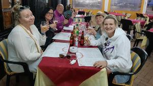All Female Panelin koomikot istuvat pitkän ravintolapöydän äärellä.