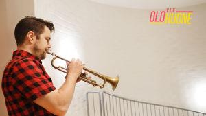 Trumpetisti-säveltäjä Verneri Pohjola soittaa trumpettia porraskäytävän ylätasanteella.