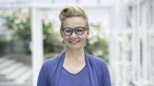 Paulina Ahokas seisoo Tampere-talossa ja hymyilee kameralle.