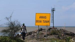Mies ohitti tsunamivaroituskyltin Banda Acehissa 21. joulukuuta 2019.
