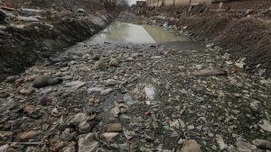 Jätemuovin saastuttama joki Pekingissä. Kuva vuodelta 2016.