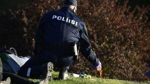 Poliisi kaataa alkoholia pullosta Hietaniemen uimarannalla kouluvuoden päätöksen juhlinnassa jota juhlittiin kauniissa auringonpaisteessa Helsingissä launatai-iltana.
