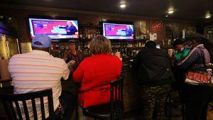 Människor sitter på barstolar vid en bardisk i Atlanta, USA. De tittar upp på en TV där man följer med rösträkning i senatsvalet i Georgia.
