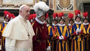 Till vänster en man i vit prästklädsel men vit kippa och ett stort kors över bröstet. Omkring honom personer i färgglada kläder.