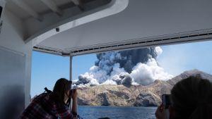 Turist fotograferar Whakaari under ett utbrott den 9 december 2019.