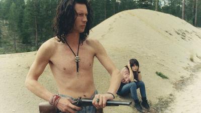 Antti Reini och kollegan Maria Heiskanen i filmen Il Capitano. Antti står barbröstad och håller i ett gevär medan Maria sitter bredvid honom och håller för öronen.