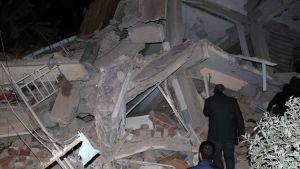 Två män går omkring på ruinerna av en byggnad som förstörts i jordskalvet.