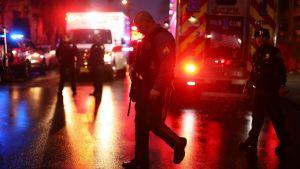 På bilden syns en polis i förgrunden och flera bakom honom gående på en mörk gata i Jersey City.