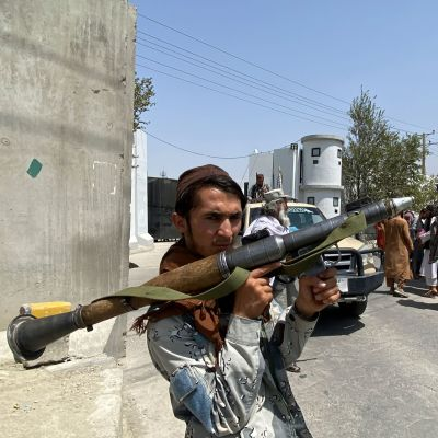 Taliban sotilas pitää raketinheitintä kädessään Afganistanin sisäministeriön edessä Kabulissa.