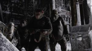 Caesar (Andy Serkis) står med vapen i hand tillsammans med sina apor i ett övergivet hus.