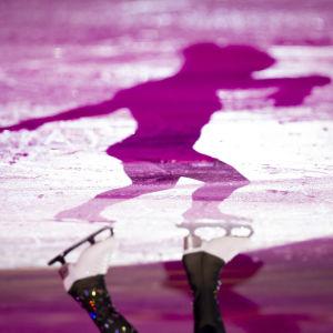 Skugga av konståkare på is.