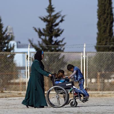En syrisk flykting med sina barn nära den stängda turkiska gränsövergången Oncunpinar. Den syriska staden Azaz ligger strax soöder om gänsövergången.